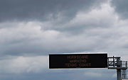 A hurricane warning sign is seen under storm clouds above a highway approaching Victoria, Texas August 25, 2017. REUTERS/Rick Wilking