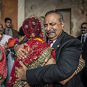 The bride bids farewell to her family during the Vidai ceremony of her Hindu wedding in Rajasthan. The Vidai traditionally marks the formal departure of the bride from her parents' home to start a new life at her husband's home.