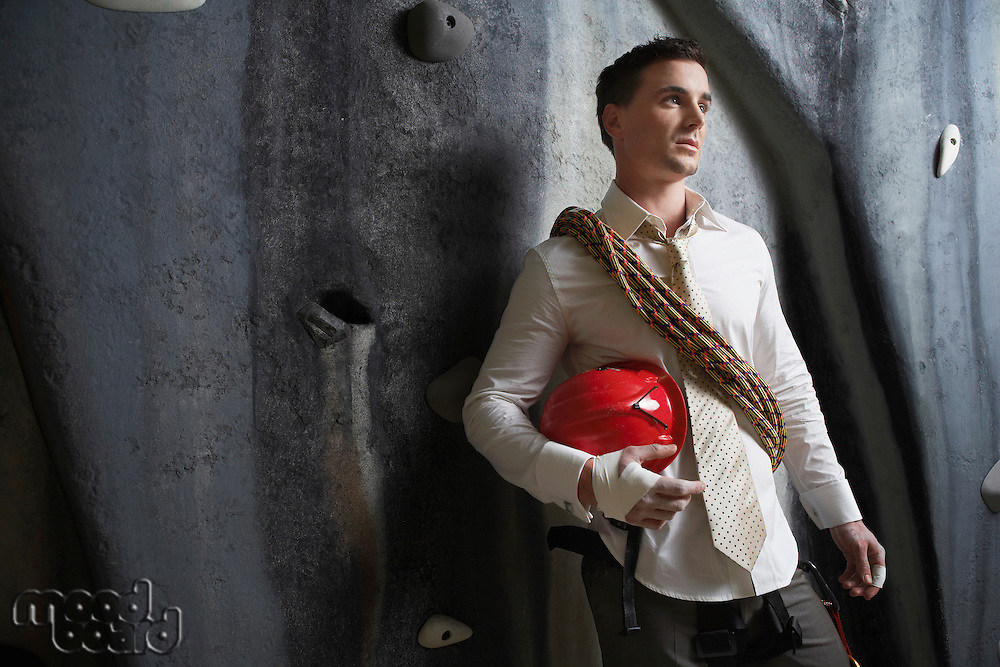 Businessman Preparing to Climb Wall