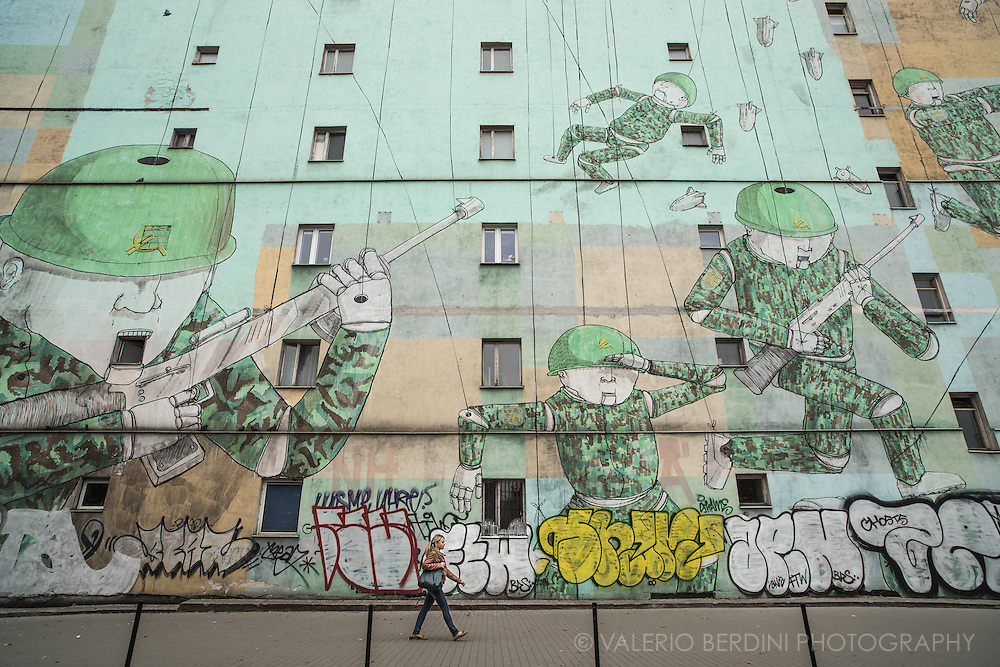 """Soldier Puppets"" by street artist Blu, on Avenue of John Paul II. This large graffiti depicts puppet soldiers. On the helmets they have a Euro symbol that merges into a communist hammer and sickle. On the soldiers arms the SS Nazi takes the form of a double dollar $$. Whoever the enemy, Warsaw new generations still face the nightmares of their past."