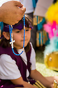 25 APRIL 2012 - PHOENIX, AZ: A girl is framed by a rosary during a prayer vigil against SB1070 at the Arizona State Capitol Wednesday. Immigrants' rights groups opposed to SB1070 and Tea Party affiliated groups that support SB1070 gathered at the state capitol in Phoenix Wednesday to express their opposition and support of the bill. SB1070 was signed by Arizona Governor Jan Brewer in April 2010. At the time it was the toughest anti-illegal immigration bill in the country. Immigrants' rights groups sued Arizona and the federal courts stopped enforcement of the bill. The bill ended up in the US Supreme Court which heard arguments Wednesday. A ruling on the bill is expected in June.     PHOTO BY JACK KURTZ