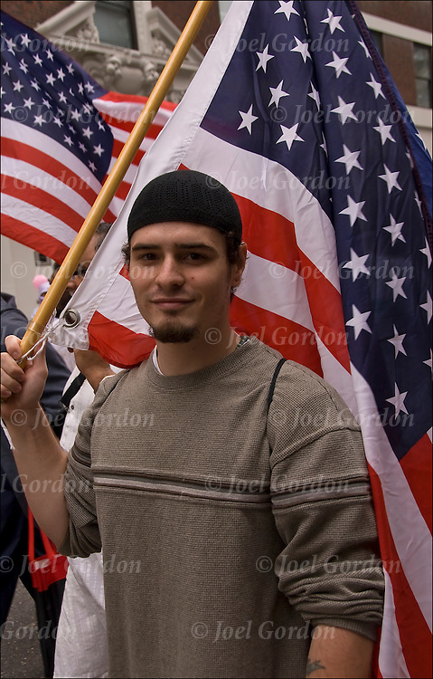 American Muslim wearing black skull cap, holding an American Flag, one of the many faces of people, showing his ethnic pride  marching in the 2010 Muslim Day Parade in New York.