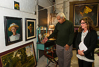 Dennis Morton talks about his paintings with Maureen Bieniarz-Pond in Morton's studio space located at the Imagine Gallery on Beacon Street West in downtown Laconia.  (Karen Bobotas/for the Laconia Daily Sun)