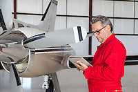 Mature aviation mechanic using tablet PC in front of airplane