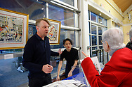 Garden City, New York, USA. March 9, 2019.  Artist Michael White (standing) helps a woman looking at his carousel watercolor prints for sale during Unveiling Ceremony of his mural of Nunley's Carousel horse closeup. Event was held at historic Nunley's Carousel in its Pavilion on Museum Row on Long Island.