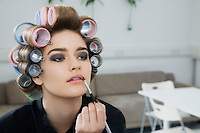 Model in Hair Curlers Applying Lip Gloss
