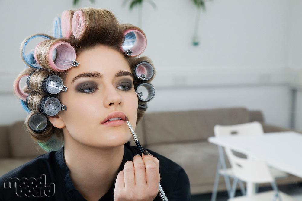 Model in Hair Curlers Applying Lip Gloss