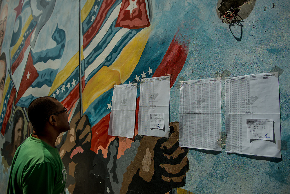 CARACAS, VENEZUELA - JULY 30, 2017:  A government supporter checks an election registry taped to a mural painted with Venezuelan and Cuban flags, to see which polling table to cast his vote at. Many fear this election will turn Venezuela similar to Cuba. Opponents of the government criticize President Maduro for calling for this election - saying the new assembly is a power grab, and will be a puppet of the President - the only candidates on the ballot are government loyalists. Critics also fear the new assembly will turn the country into a dictatorship, re-write the constitution and wipe out the democratically elected and opposition controlled congress. There have been widespread reports of voter intimidation, and of the government threatening state workers and citizens that receive government benefits like subsidized food - who report the government telling them they are obligated to vote, and if they don't, they will lose their jobs and benefits. Thousands have taken to the streets to protest the election in the days leading up to the July 30th vote.  PHOTO: Meridith Kohut for The New York Times