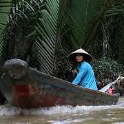 Traditional boats carry freight on the Mekong River and canals Ben Tre on the Mekong Delta, Vietnam.    Photography by Jose More