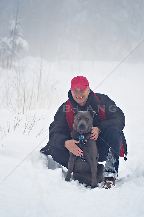 mature man with his dog in the snow