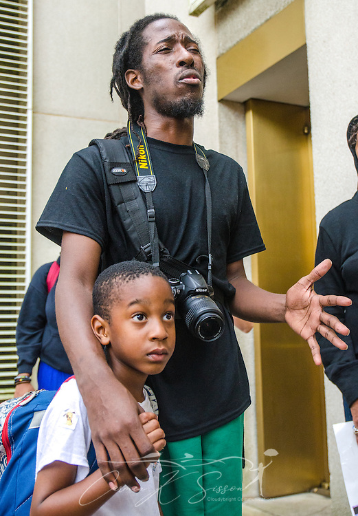 """Dream Defender Travis Roberts stands with Sevyn Coleman, 5, leading protestors in a song July 20, 2013, outside the Florida Capitol Complex executive tower. Dream Defenders, a youth-led activist group, sequestered itself within the building July 16, demanding a special legislative session to address concerns over racial profiling and Florida's """"stand-your-ground"""" self-defense law. The group formed in 2012 after the fatal shooting of 17-year-old Trayvon Martin.  (Photo by Carmen K. Sisson/Cloudybright)"""