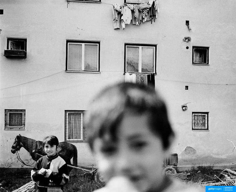 Children play in a housing estate in the heart of  the small Romanian town of  Copsa Mica, Transylvania, Romania. Copsa Mica was once described as the most polluted town in Europe. May 8, 2008. Photo Tim Clayton....Copsa Mica, a small industrial town deep in Transylvania, Romania, was described during the 1990s as the most polluted town in Europe with lead levels reaching were more than 1000 times the allowable International limits and life expectancy nine years shorter than the National average...The pollution was caused entirely by two factories, Carbosin produced black for dies and tires and closed in 1993 while Sometra, a nonferrous smelter is still operational today...The pollution was so bad sheep were black, covered in soot and health officials advised against eating livestock or vegetables and drinking the water or milk...The Communist rule of Nicolae Ceausescu is blamed for the widespread environmental degradation that left industrial parts of Romania in ecological disaster. Industry was situated in a way to concentrate pollution in small areas leaving the rest of the country relatively free of pollution. Copsa Mica in particular was left an environmental disaster...The pollution caused a direct affect on human health with widespread Lung disease, Impotency, the highest infant mortality rate in Europe, Lead poisoning and behavioral problems...Fifteen years on since the closure of Carbosin in 1993, the factory skeleton remains as part of the towns bleak landscape, Unfinished communist style housing blocks still stand in the heart of the towns housing estate. The town's inhabitants are still trying to recover from the long lasting effects of pollution...Recent survey's found the soil contained so much lead that it was 92 times above the permitted level; the vegetation had a lead content 22 times above the permitted level. While toxins have penetrated at least one meter (three feet) into the soil leaving the entire food chain in the area cont