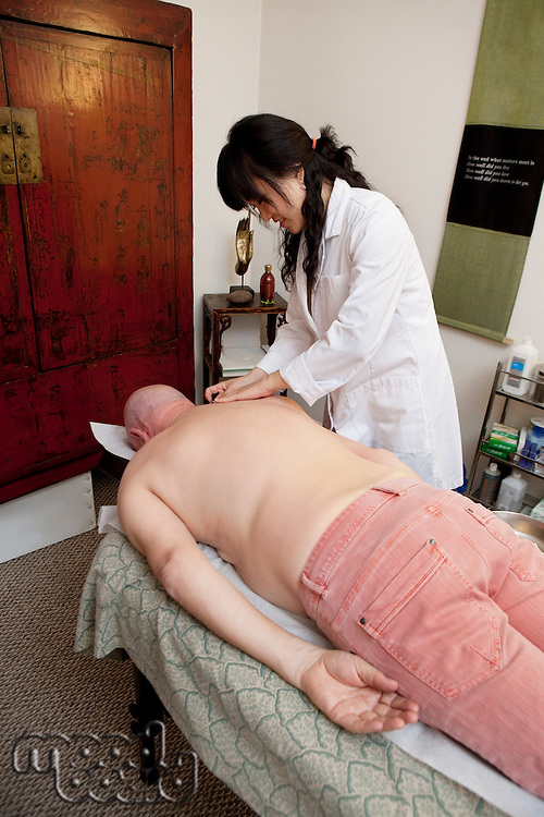 Senior man lying on front for cupping treatment