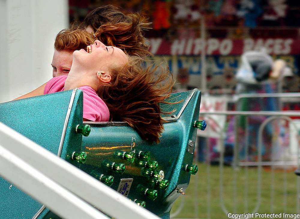 HEATHER AINSWORTH/Obersver-Dispatch.Karley Redner, 14, throws her head back while taking a ride on the Sizzler with Ashley McCanney, left, and Levi Dieterle, not pictured, Monday at the  Boonville Oneida County Fair.