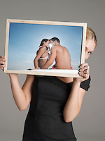 Young businesswoman peeking from behind photograph of couple at beach against gray background