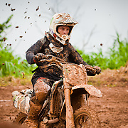 Mud flying from the back wheel of a motorcycle biker on an extremely muddy motocross outdoor track in Belmopan, Belize.