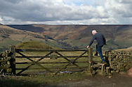 Walker climbing over a stile above Edale. Peak District National Park Derbyshire....