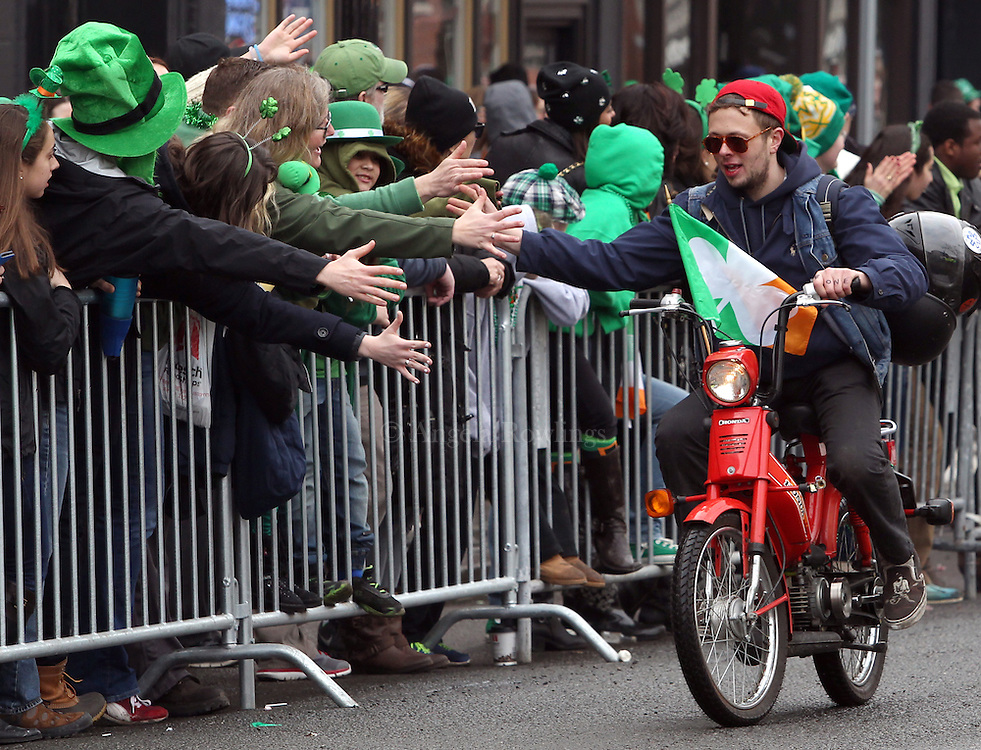 (Boston, MA - 3/15/15) A member of a moped gang [how a member described it] high-fives the crowd during the St. Patrick's Day Parade in South Boston, Sunday, March 15, 2015. Staff photo by Angela Rowlings.