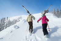 Teenage couple (16-17) holding skis hiking up slope back view.