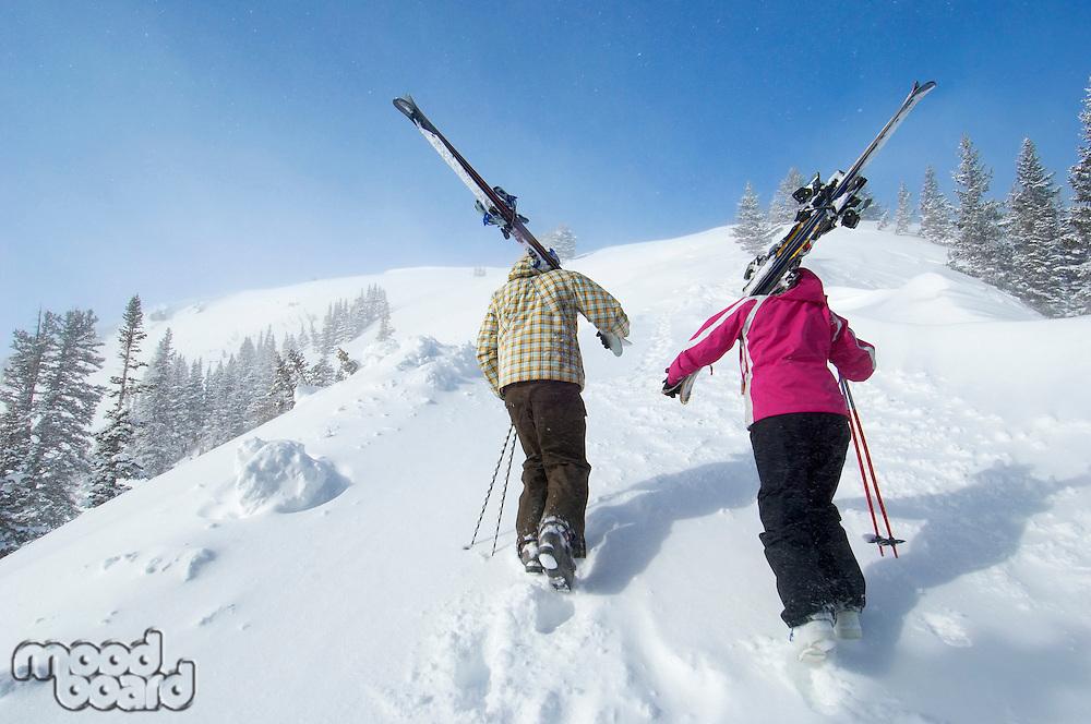 Teenage couple (16-17) holding skis hiking up slope back view.