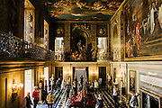 Visitors inside Chatsworth House. Mural on ceiling and wall by French artist, Louis Laguerre (1663-1721). <br /> <br /> Chatsworth House is a stately home in Derbyshire. It is the seat of the Duke of Devonshire and has been home to the Cavendish family since 1549. Standing on the east bank of the River Derwent, Chatsworth looks across to the low hills that divide the Derwent and Wye valleys. The house, set in expansive parkland and backed by wooded, rocky hills rising to heather moorland, contains a unique collection of priceless paintings, furniture, Old Master drawings, neoclassical sculptures, books and other artefacts. Chatsworth has been selected as the United Kingdom's favourite country house several times.