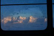 Sonnige Berggipfel der Freiburger Vorlapen gesehen durch das vereiste Fenster der Luftseilbahn Moléson. Vu des préalpes fribourgeoises ensoleillés à travers la vitre gelée du télécabine du Moléson