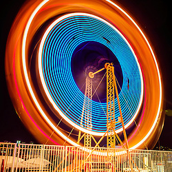 Balboa Fun Zone Ferris Wheel at night picture. The Ferris Wheel is part of the Balboa Fun Zon which is an amusement park located on Balboa Peninsula in Newport Beach California. The Ferris Wheel is spinning and the lights are motion blurred.