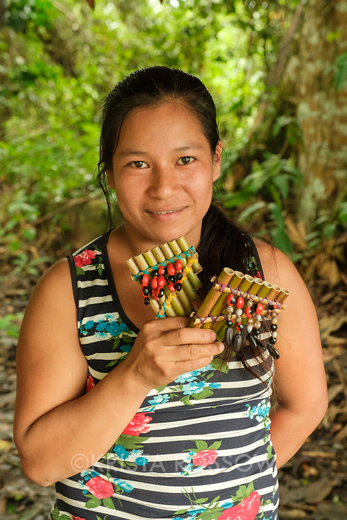 A young woman vendor sells bamboo flutes decorated with seeds at Amazon Natural Park in the Peruvian Amazon.