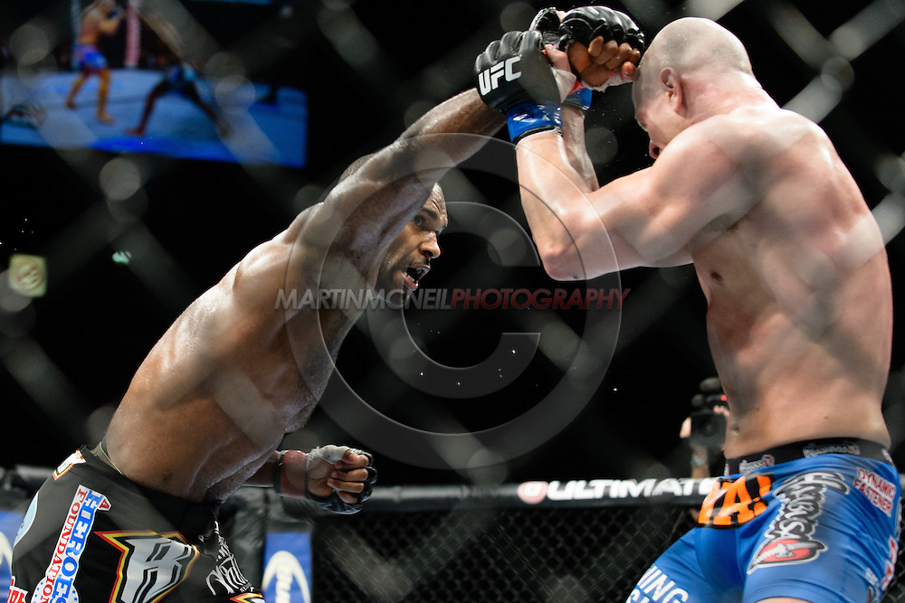 """MANCHESTER, ENGLAND, OCTOBER 26, 2013: Jimi Manuwa (black shorts) and Ryan Jimmo (blue trunks) compete during """"UFC Fight Night 30: Machida vs. Munoz"""" inside Phones4U Arena in Manchester, England (© Martin McNeil)"""