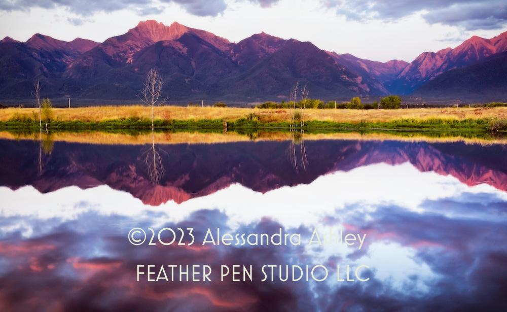Sunset reflection of Rocky Mountains at Ninepipe National Wildlife Refuge, northwest Montana, USA.