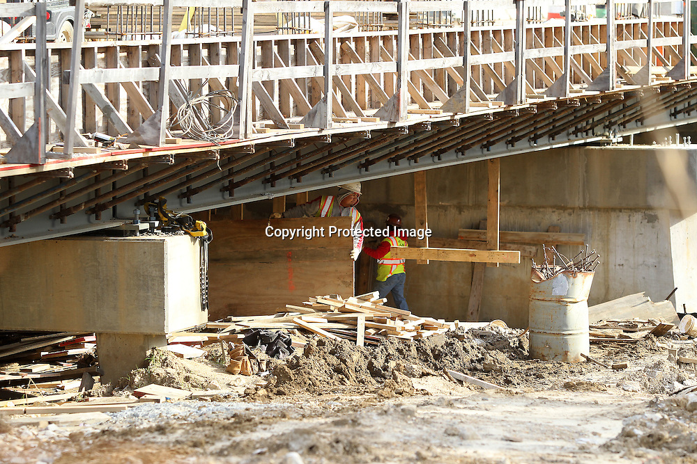 Adam Robison   BUY AT PHOTOS.DJOURNAL.COM<br /> Workers remove lumber used in framing up the new bridge at Mud Creek on East Main Street Monday morning in Tupelo.