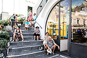 "03 August 2017, Capri Italy - Tourists take cover from the sun seated on the staircase of the ""Piazzetta"", Umberto I square in the center of Capri island."