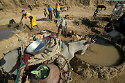 To water their animals, Amna Mustapha (wearing yellow dress) and a cousin must first dip plastic containers into a six-foot well. They then pour the water into a low earthen-walled pool from which the animals drink (the millet stalks at the edge of the trough keep the cascading water from breaking down the wall). Families take turns using the pools, which must be rebuilt often and will ultimately wash away during the rainy season. (Supporting image from the project Hungry Planet: What the World Eats).