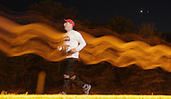 Augusta, New Jersey - A runner on the course at night in the  72-hour race during the 3 Days at the Fair races at Sussex County Fairgrounds on May 10, 2012. The runner is lit by the light from a photographer's flash; the blurry lines are from his movement during the long exposure.