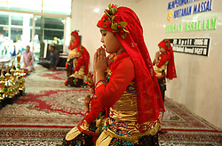 Young female performers dressed in traditional costume dance at the mass circumcision timed to honor the Prophet Mohammed's birthday in Bandung, Indonesia on April 23, 2006. All the girls were circumcised in years prior. The families of 248 girls were given money to have their children circumcised at this event. While religion was the main reason for circumcisions, it is believed by some locals that a girl who is not circumcised would have unclean genitals after she urinates which could lead to cervical cancer. It is also believed if one prays with unclean genitals their prayer won't be heard. The practitioners used scissors to cut the hood and tip of the clitoris. The World Health Organization has deemed the ritual unnecessary and condemns such practices.