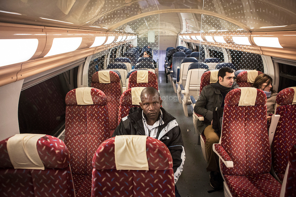 BEAUSOLEIL, FRANCE - 17 NOVEMBER 2014: A migrant takes the train that goes from Ventimiglia to Nice, taken by migrants that want to cross the border from Italy to France, in Beausoleil, France, on November 17th 2014. They are trying to call their friend that was caught by the French border patrol in Menton that pushed him back to Italy. <br /> <br /> The Ventimiglia-Menton border is the border between Italy and France crossed by migrants who decide to continue their journey up north towards countries such as Germany, Sweden, The Netherlands and the UK where the process to receive the refugee status or humanitarian protection is smoother and faster. in Ventimiglia, Italy, on November 17th 2014.