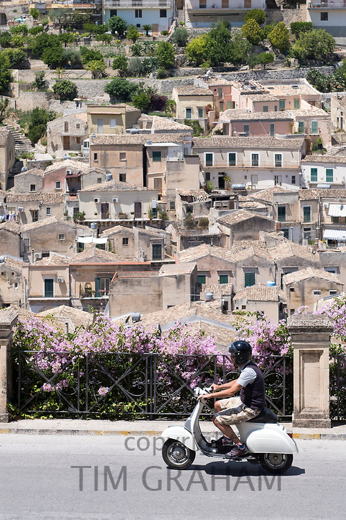 Man riding motorscooter in hill city of Modica Alta looking towards Modica Bassa, Sicily, Italy
