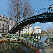 Passerelle Bichat, a cast iron arched pedestrian footbridge built late 19th century in the Recollets basin, and the Ecluses des Recollets lock, between the Quai de Valmy and Quai de Jemmapes, over the Canal Saint-Martin in the 10th arrondissement of Paris, France. The Canal Saint-Martin is a 4.6km long waterway between the Canal de l'Ourcq and river Seine, built 1802-25 to provide a fresh water source to the city and provide a trade route for canal barges. Picture by Manuel Cohen