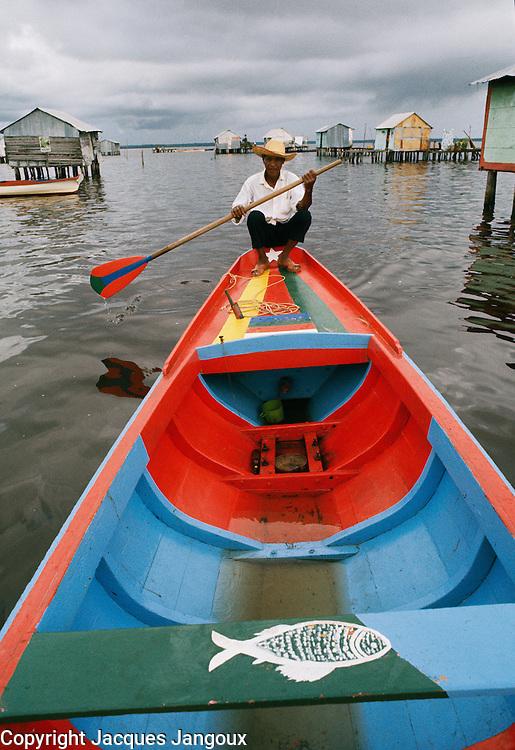 Dweller of stilt houses in Lake Maracaibo in Venezuela paddling, using his fishing boat for transportation.