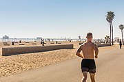 Man Running On Huntington Beach Boardwalk With Pier In Background