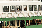 People look out the windows of the Star Ferry as it crosses Victoria Harbor in Hong Kong. Star Ferry boats have been carrying passengers from Hong Kong Island to Kowloon and back since 1888.