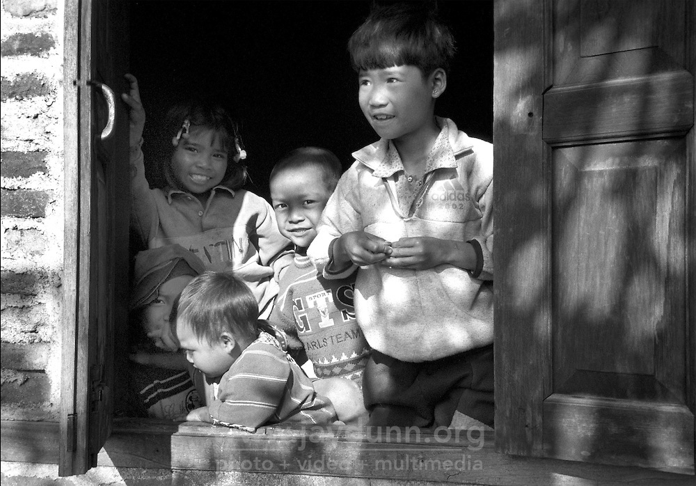 BURMA (MYANMAR), Shan State, Peinnebin. 2006. Palaung children watch the whole village gather outside their window after the wedding ceremony.