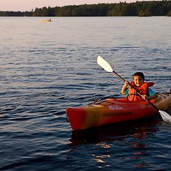 A young boy kayaks on Umbagog Lake at Umbagog Lake State Park, Cambridge, New Hampshire.