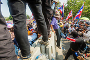 "09 DECEMBER 2013 - BANGKOK, THAILAND: Anti-government protestors scramble over barricades blocking the roads in front of Government House in Bangkok. Thai Prime Minister Yingluck Shinawatra announced she would dissolve the lower house of the Parliament and call new elections in the face of ongoing anti-government protests in Bangkok. Hundreds of thousands of people flocked to Government House, the office of the Prime Minister, Monday to celebrate the collapse of the government after Yingluck made her announcement. Former Deputy Prime Minister Suthep Thaugsuban, the organizer of the protests, said the protests would continue until the ""Thaksin influence is uprooted from Thailand."" There were no reports of violence in the protests Monday.      PHOTO BY JACK KURTZ"
