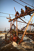 Fishermen at Wagenia Falls (or Boyoma Falls) raise a bamboo basket from the rapids, near Kisangani, DR Congo.