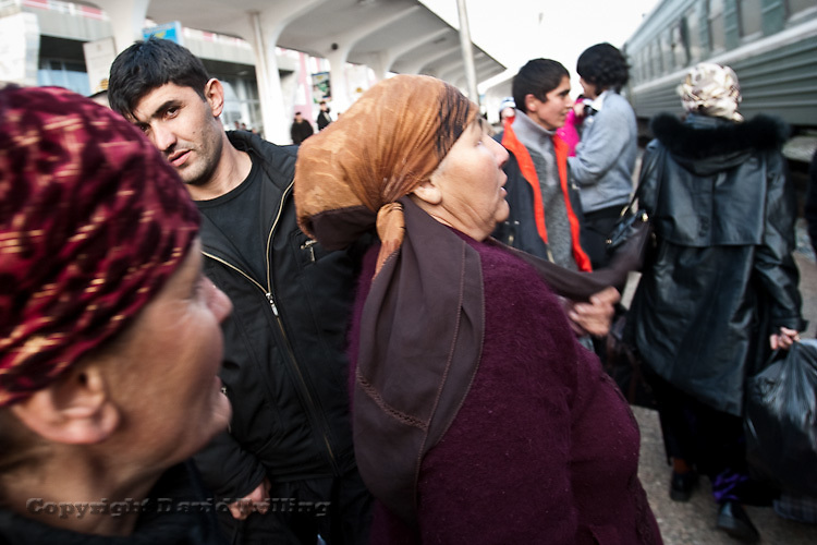 Tajikistan: Women wait as a train from Moscow arrives packed with young men. February 2009.