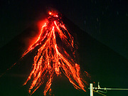 """22 JANUARY 2018 - LEGAZPI, ALBAY, PHILIPPINES: Lava flows from the cone of the Mayon volcano Monday night, as seen from Legazpi, about 12 kilometers from the volcano. There were a series of eruptions on the Mayon volcano near Legazpi Monday. The eruptions started Sunday night and continued through the day. At about midday the volcano sent a plume of ash and smoke towering over Camalig, the largest municipality near the volcano. The Philippine Institute of Volcanology and Seismology (PHIVOLCS) extended the six kilometer danger zone to eight kilometers and raised the alert level from three to four. This is the first time the alert level has been at four since 2009. A level four alert means a """"Hazardous Eruption is Imminent"""" and there is """"intense unrest"""" in the volcano. The Mayon volcano is the most active volcano in the Philippines. Sunday and Monday's eruptions caused ash falls in several communities but there were no known injuries.   PHOTO BY JACK KURTZ"""