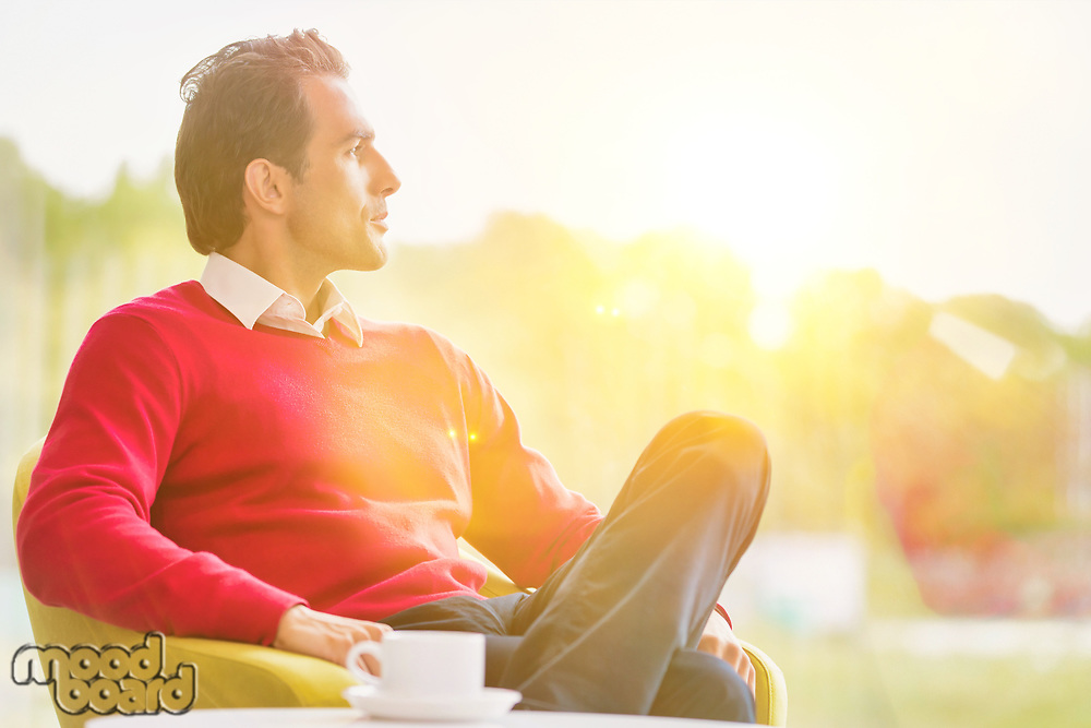 Young thoughtful businessman sitting while drinking coffee in lobby with lens flare