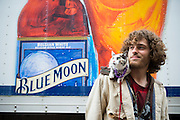 A cat with Mardi Gras beads around its neck sits on a young man's shoulder on Bourbon Street in New Orleans, Louisiana. A Blue Moon beer delivery truck is in the background.