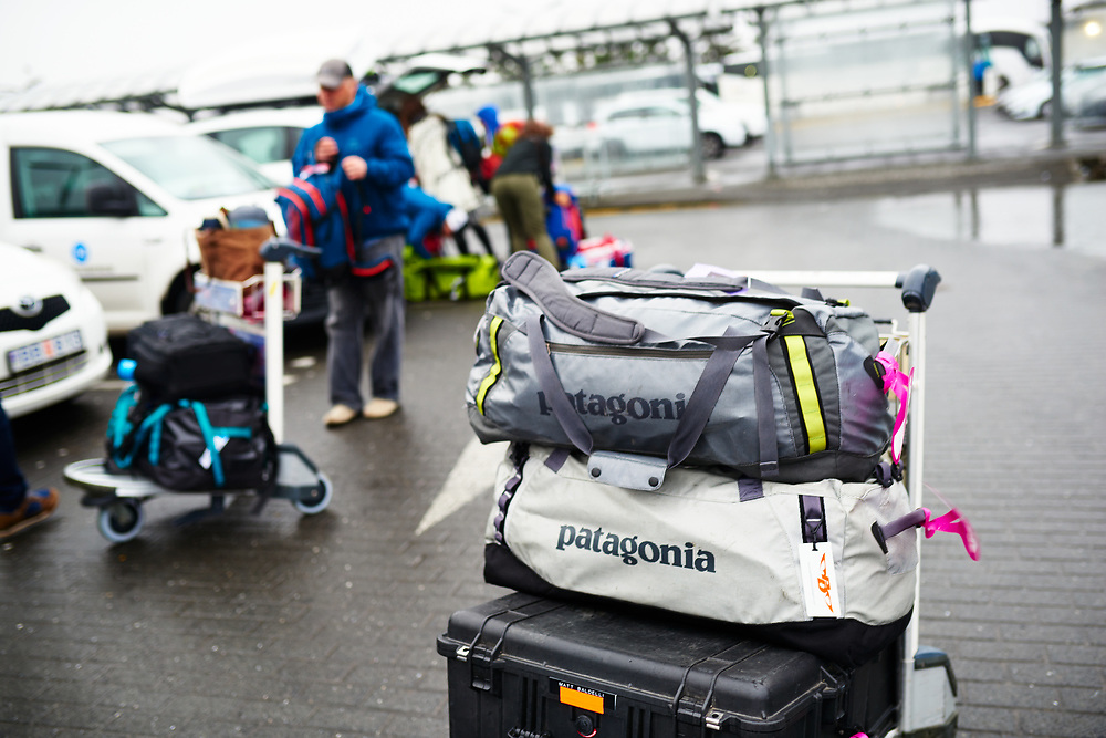 Patagonia black hole duffle bag sitting on the cart at Reykjavik Airport parking lot